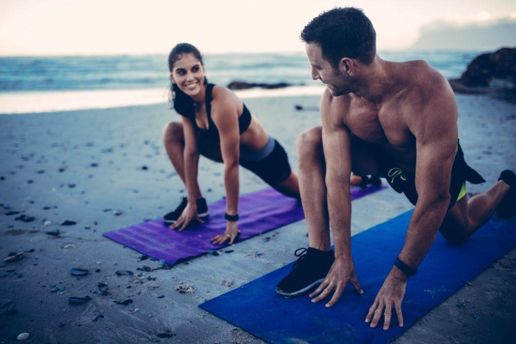 people doing yoga on a beach